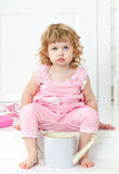 Pequeña muchacha rizada linda en un vestido rosado con los lunares que se sientan en el estilo blanco de Provence del pórtico Fotos de archivo