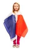 Pequeña muchacha sonriente envuelta en la bandera de Francia Foto de archivo