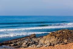 Pequeña playa del azul de las ondas de las personas que practica surf Fotografía de archivo