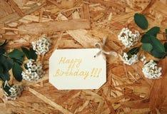 Pequeña tarjeta de cumpleaños amarilla del deseo con las flores blancas y las hojas del verde en el fondo de madera de la textura Fotos de archivo libres de regalías