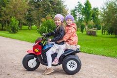 Pequeñas hermanas adorables que se sientan en la motocicleta del juguete Imágenes de archivo libres de regalías