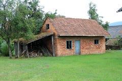 Pequeno abandonou a casa do tijolo vermelho com janelas e as portas quebradas ao lado da garagem de madeira destruída velha cerca imagens de stock