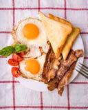 Pequeno almoço com bacon e os ovos fritados Foto de Stock