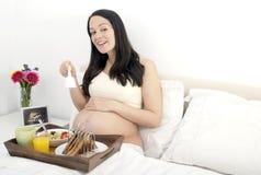 Pequeno almoço da mulher gravida na cama Fotografia de Stock Royalty Free