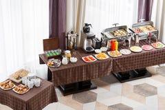 Pequeno almoço no hotel Tabela de bufete com os convidados de espera do dishware imagem de stock royalty free