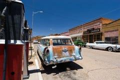 Pequeno-cidade retro com posto de gasolina e os carros velhos Imagem de Stock