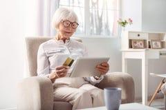 Pequeno mulher idosa que faz o pagamento em linha para o artigo foto de stock