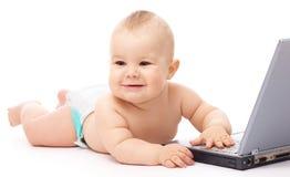 Pequeño bebé con la computadora portátil Imagen de archivo