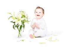 Pequeño bebé divertido con las flores del lirio Foto de archivo libre de regalías