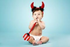 Pequeño bebé divertido con los cuernos y el tridente del diablo Imagen de archivo