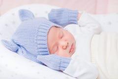 Pequeño bebé durmiente que lleva el sombrero azul hecho punto con los oídos Imagenes de archivo