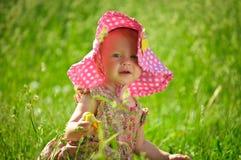 Pequeño bebé lindo en el sombrero que se sienta en la hierba Fotografía de archivo libre de regalías