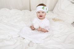 Pequeño bebé lindo en la ropa blanca, sentándose en la cama, jugando con el juguete Imagen de archivo