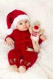 Pequeño bebé lindo, vestido en guardapolvo rojo con el sombrero de santa Fotografía de archivo