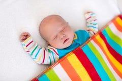 Pequeño bebé que duerme debajo de la manta colorida Imágenes de archivo libres de regalías