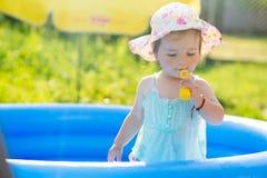 Pequeño bebé que juega con los juguetes en piscina inflable Foto de archivo libre de regalías