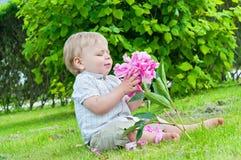 Pequeño bebé que sostiene una flor en su mano Fotografía de archivo