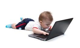 Pequeño bebé que usa la computadora portátil Fotos de archivo