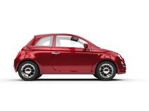 Pequeño Cherry Red Metallic Economy Car - vista lateral Imágenes de archivo libres de regalías