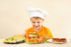 Pequeño cocinero divertido en el sombrero de los cocineros que prepara la hamburguesa Fotografía de archivo libre de regalías