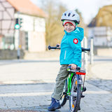 Pequeño montar a caballo preescolar del muchacho del niño con su primera bici verde Fotografía de archivo libre de regalías