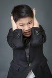Pequeño muchacho asiático en trastorno negro del traje, cara de la depresión Imágenes de archivo libres de regalías