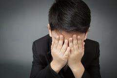 Pequeño muchacho asiático en trastorno negro del traje, cara de la depresión Foto de archivo