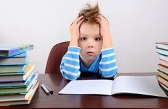 Pequeño muchacho cansado que se sienta en un escritorio y que lleva a cabo las manos a la cabeza Fotografía de archivo libre de regalías