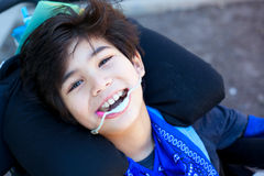 Pequeño muchacho discapacitado hermoso en la silla de ruedas, sonriendo para arriba en la cámara Imagenes de archivo