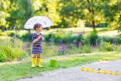 Pequeño niño adorable en botas y paraguas amarillos de lluvia en summe Fotos de archivo libres de regalías