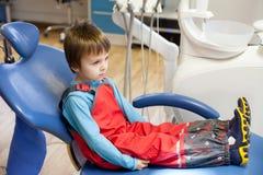 Pequeño niño asustado, muchacho, sentándose en la silla del dentista, esperando Fotografía de archivo libre de regalías