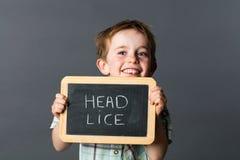 Pequeño niño de risa que advierte sobre los piojos principales para luchar contra Imágenes de archivo libres de regalías