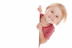 Pequeño niño detrás de la tarjeta blanca Fotos de archivo libres de regalías