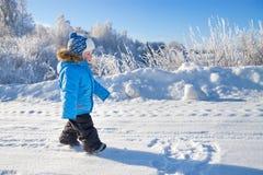 Pequeño niño feliz el muchacho en paseo en el invierno en parque Imagen de archivo libre de regalías