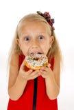 Pequeño niño femenino hermoso con el pelo rubio largo y el vestido rojo que come el buñuelo del azúcar con los desmoches encantad Imágenes de archivo libres de regalías
