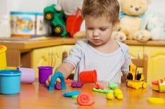 Pequeño niño que juega el plasticine Imágenes de archivo libres de regalías