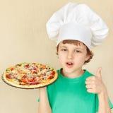 Pequeño niño sonriente en sombrero de los cocineros con la pizza apetitosa cocinada Imágenes de archivo libres de regalías