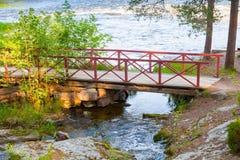 Pequeño puente de madera con las verjas rojas Fotografía de archivo