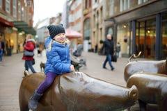 Pequeño turista lindo que se sienta en la escultura popular de la familia del cerdo, del porquero y de su perro en Bremen Foto de archivo