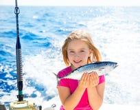 Pequeños atunes del niño de la muchacha del atún rubio de la pesca felices con la captura Imagenes de archivo