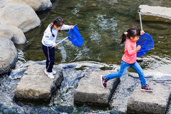 Pequeños estudiantes para recoger la basura del rive Imagen de archivo libre de regalías