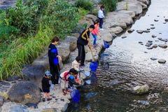 Pequeños estudiantes para recoger la basura del rive Imagen de archivo