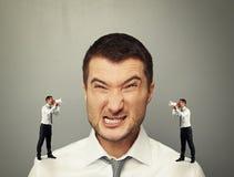Pequeños hombres que gritan en el hombre enojado grande Fotografía de archivo libre de regalías