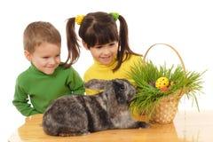 Pequeños niños con el conejo de pascua Foto de archivo libre de regalías