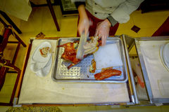 PEQUIM, CHINA - 29 DE JANEIRO DE 2017: Cozinheiro chefe profissional que corta um pato de peking tradicional famoso usando a faca Fotos de Stock Royalty Free