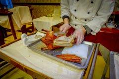 PEQUIM, CHINA - 29 DE JANEIRO DE 2017: Cozinheiro chefe profissional que corta um pato de peking tradicional famoso usando a faca Imagens de Stock