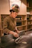 Pequim, China - 9 de junho de 2018: Um cozinheiro chefe fêmea chinês está cozinhando o jantar na frente dos visitantes do restaur imagem de stock