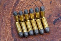 Período ocidental selvagem dos cartuchos do revólver no fundo de madeira Imagens de Stock Royalty Free