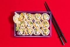 per andare contenitore di sushi sulla tovaglia rossa con i bastoncini Immagine Stock