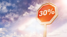 30 Per Cent, text on red traffic sign. 30 Per Cent, text on red traffic stop sign in front of cloudy blue sky with lens flares Stock Photos
